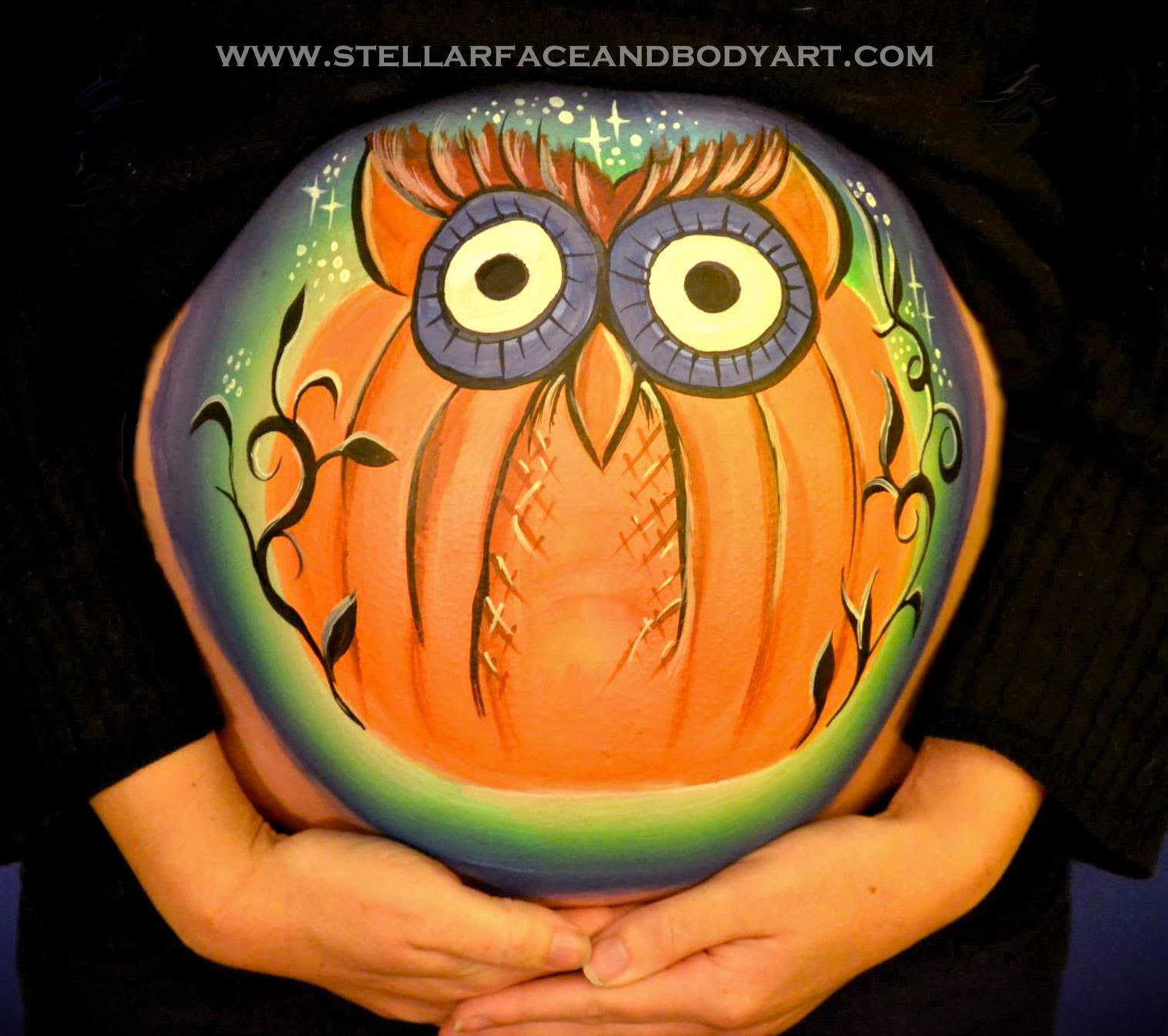 A belly painting of an orange and purple owl.