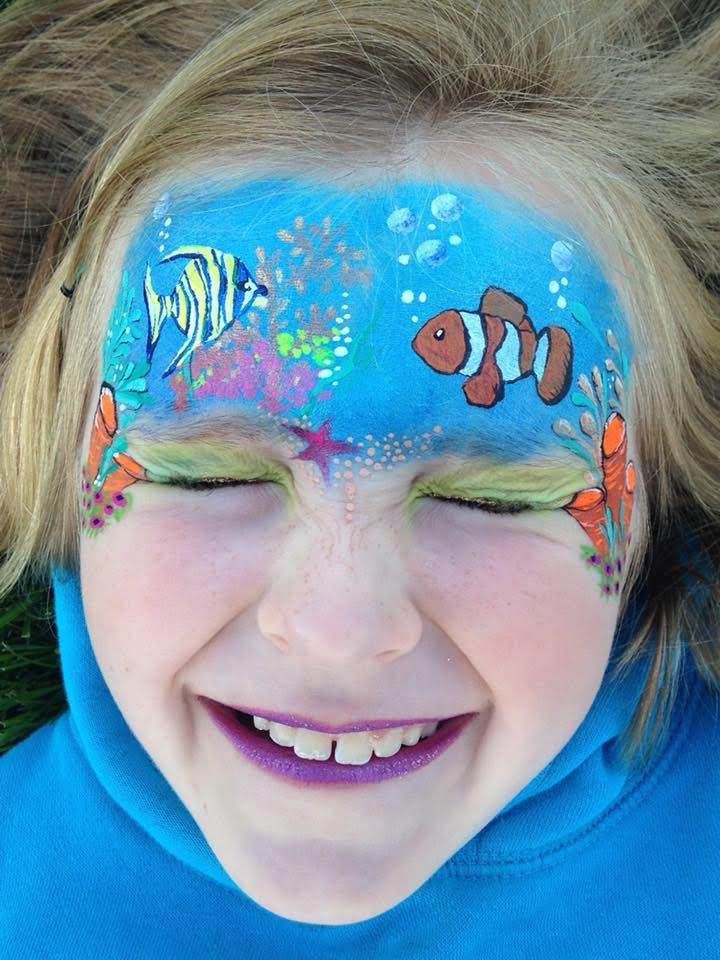 Blue forehead face painting with coral, a clown fish and an angel fish.